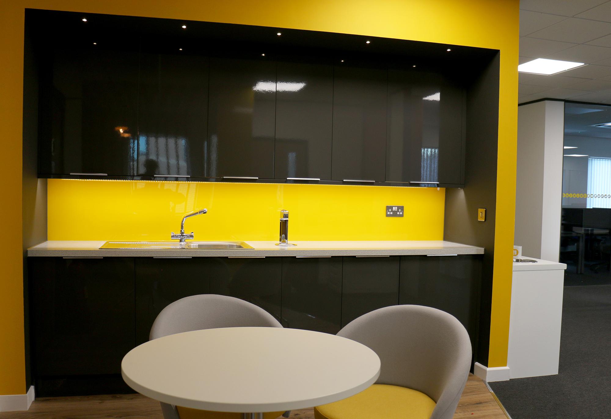 Office kitchen with bright yellow splashback