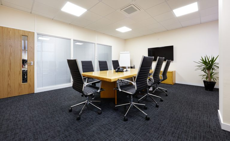 wooden boardroom table with black chairs and TV mounted on wall