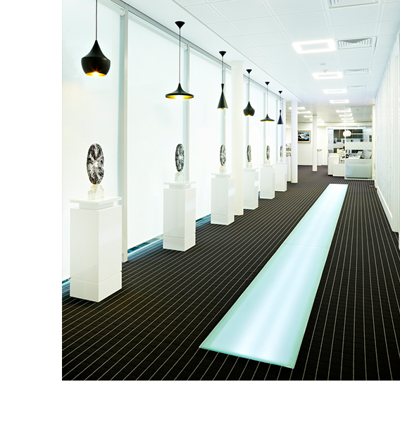 long wide corridor with stripy carpet, black pendant lights, illumintae section of floor and plinths eith trophies on