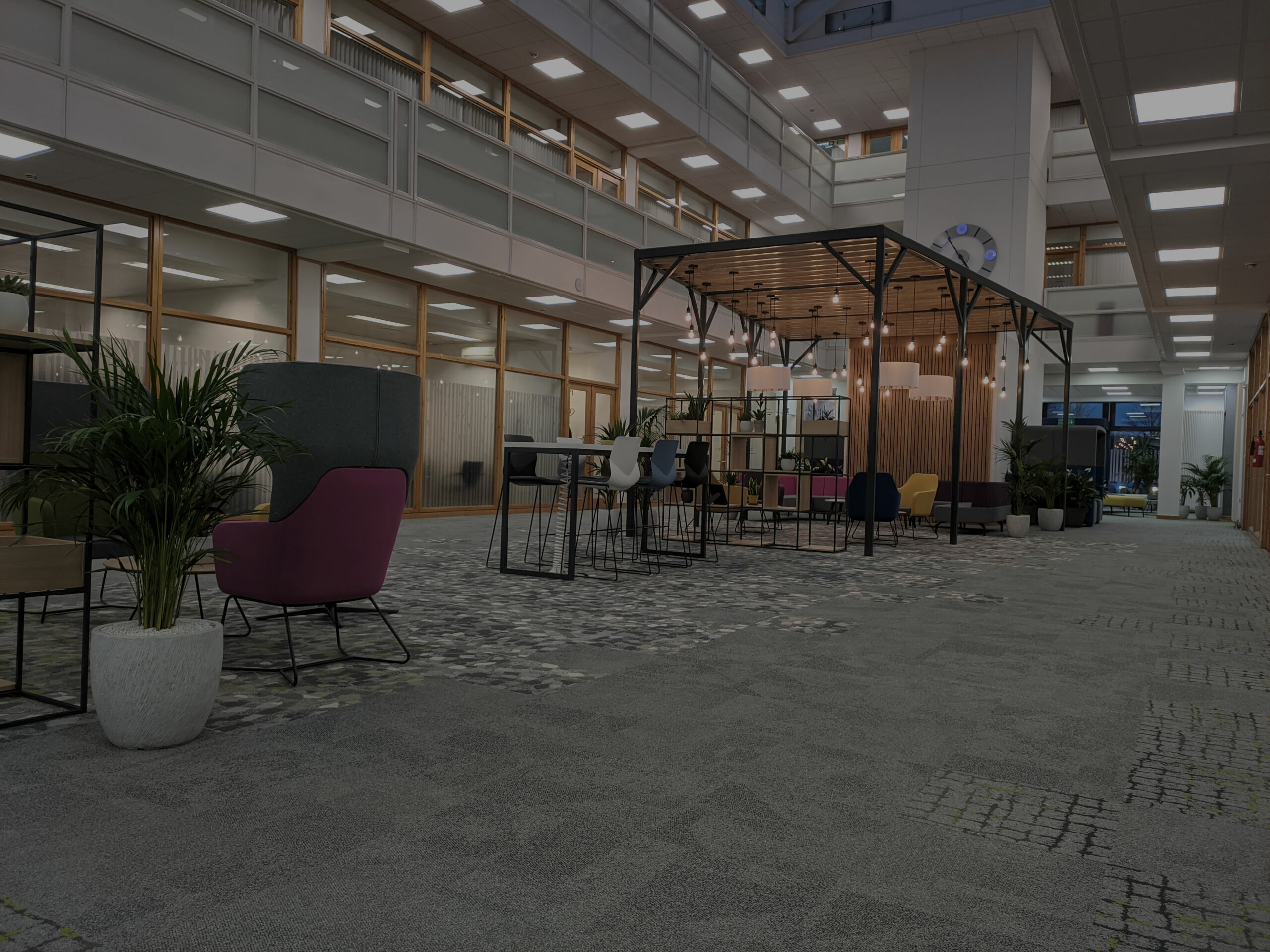 atrium in centre of large office block. Timber and metal structure with suspended lighting and colourful chairs