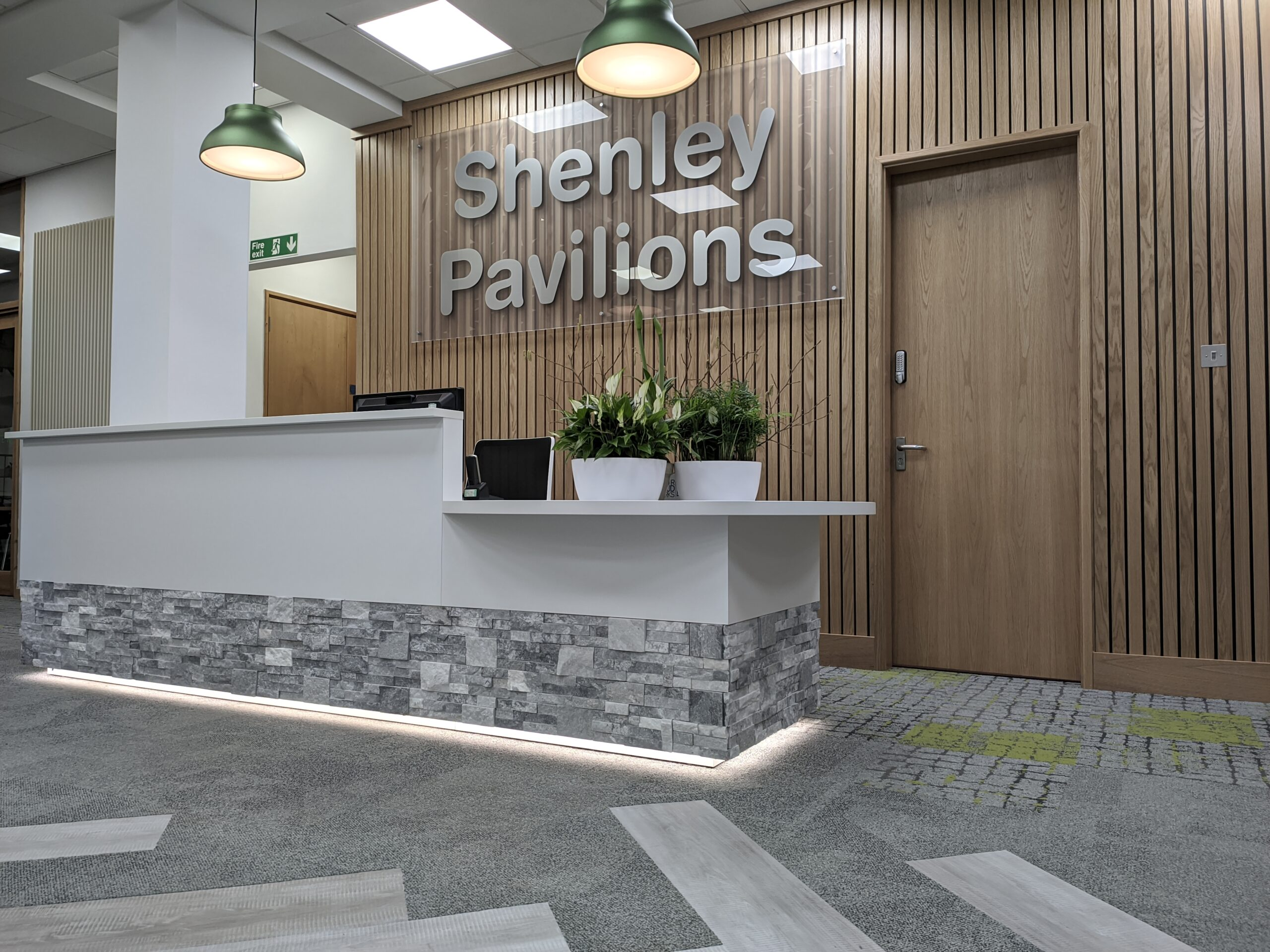 White reception counter in front of timber clad wall