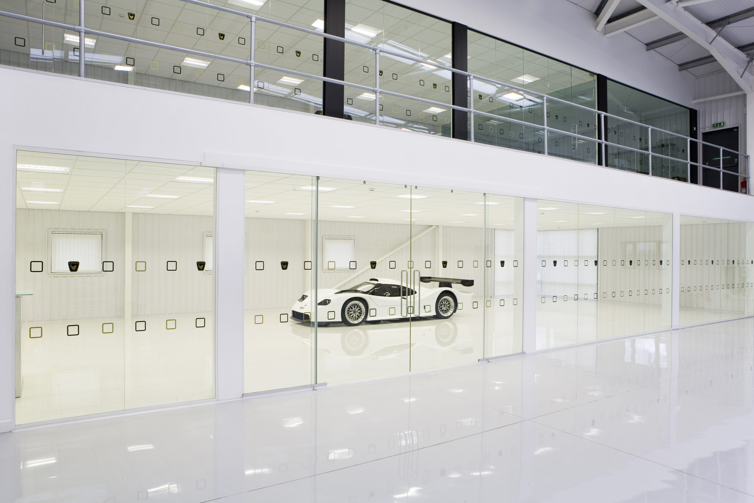 a white sports car behind at wall of glass with square patterned manifestations