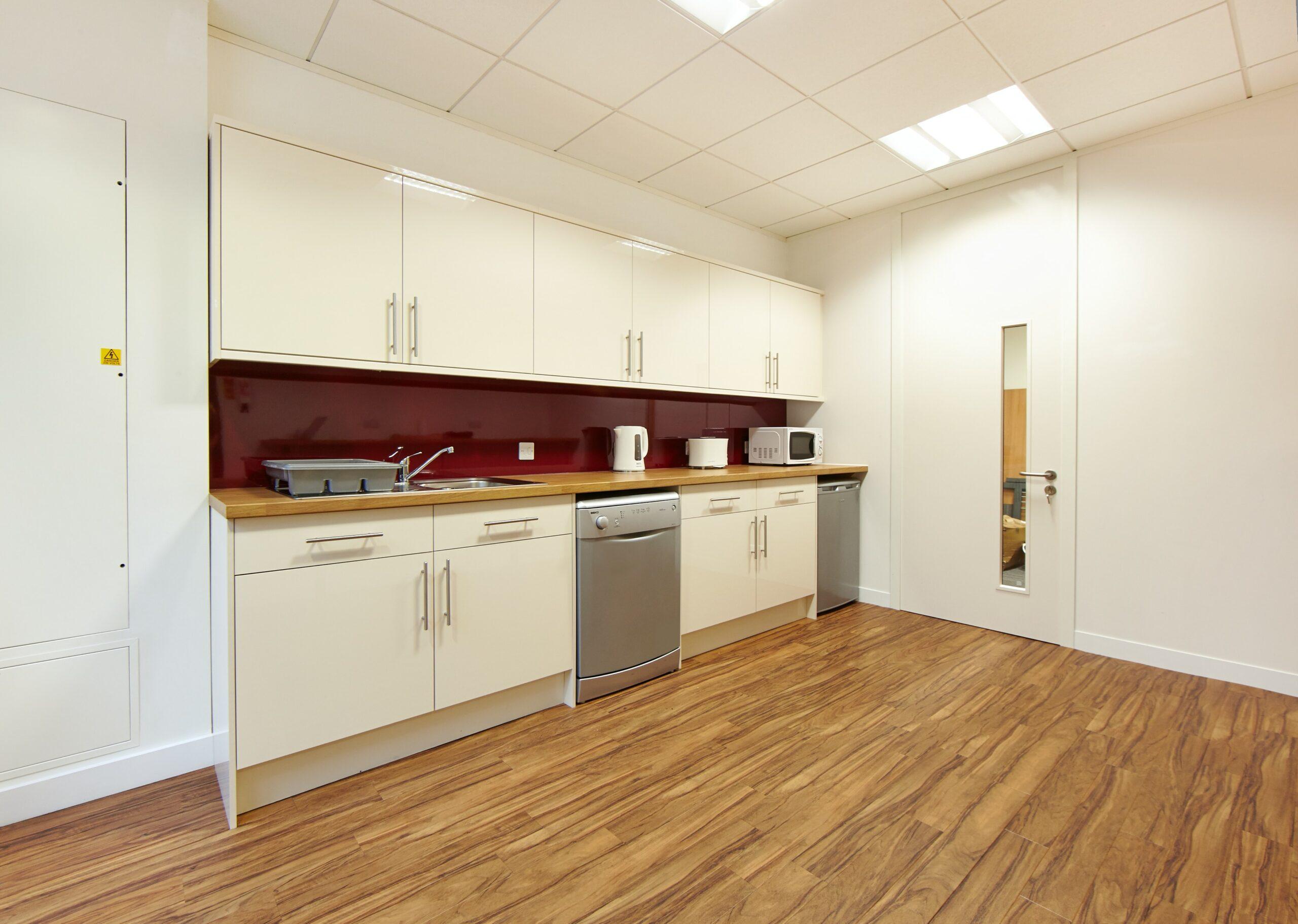 white gloss kitchen cabinets with wooden worktop and dark red splashback