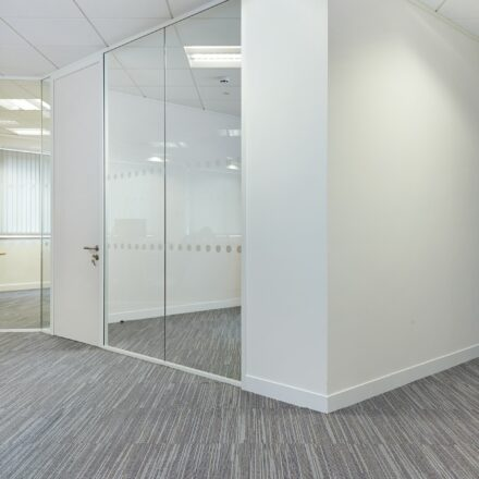 White corner partitioning with floor to ceiling glazed panels and grey carpet.