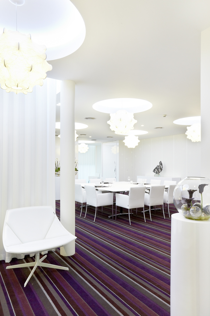 purple stripey carpet with white table and chairs. white handing lights