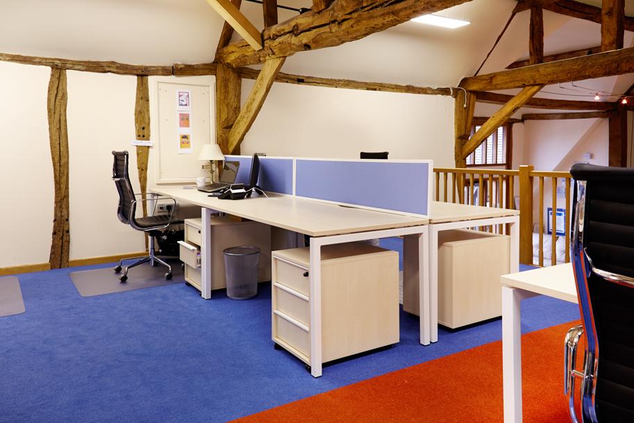 beech desks with blue and orange carpet. Traditional oak beamed ceiling