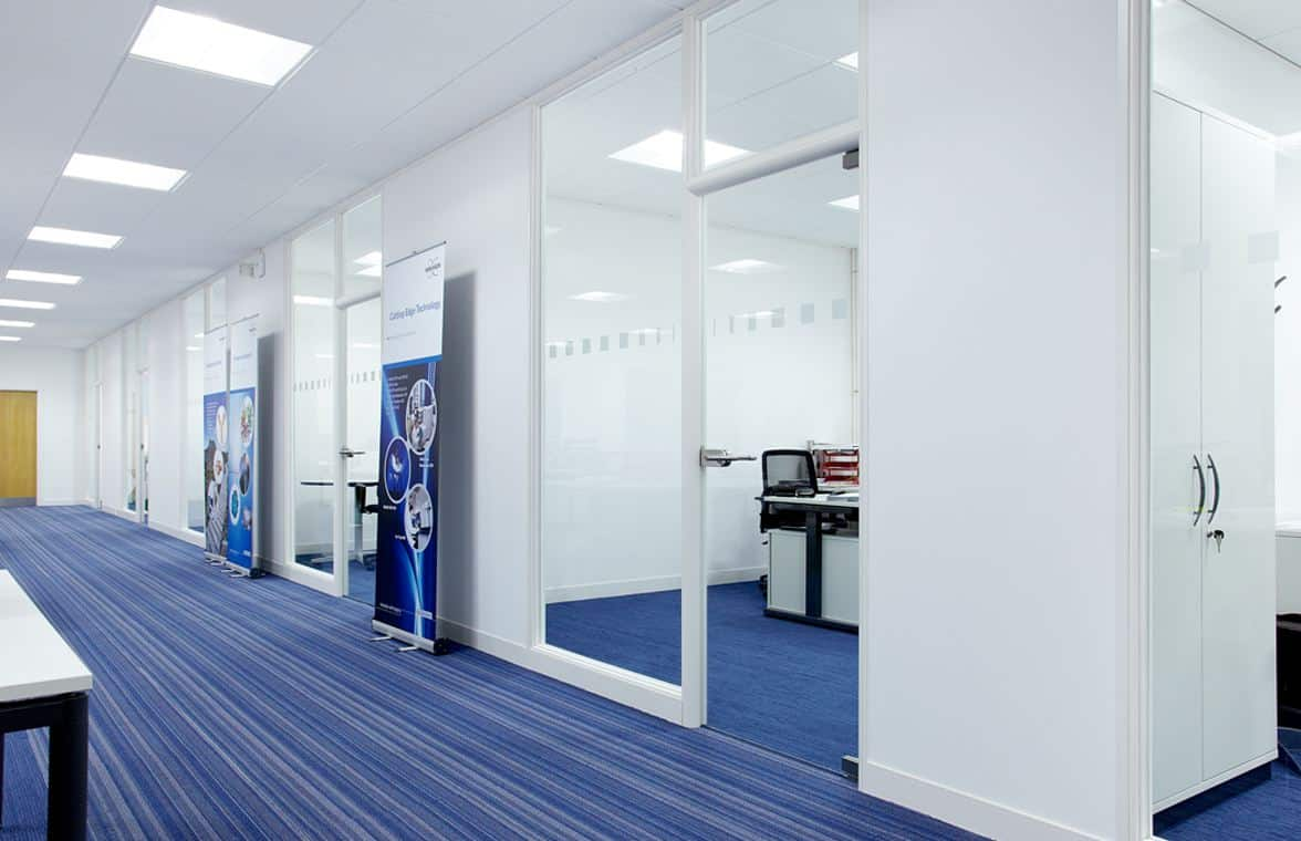blue carpeted corridor with white partitioning with glazing