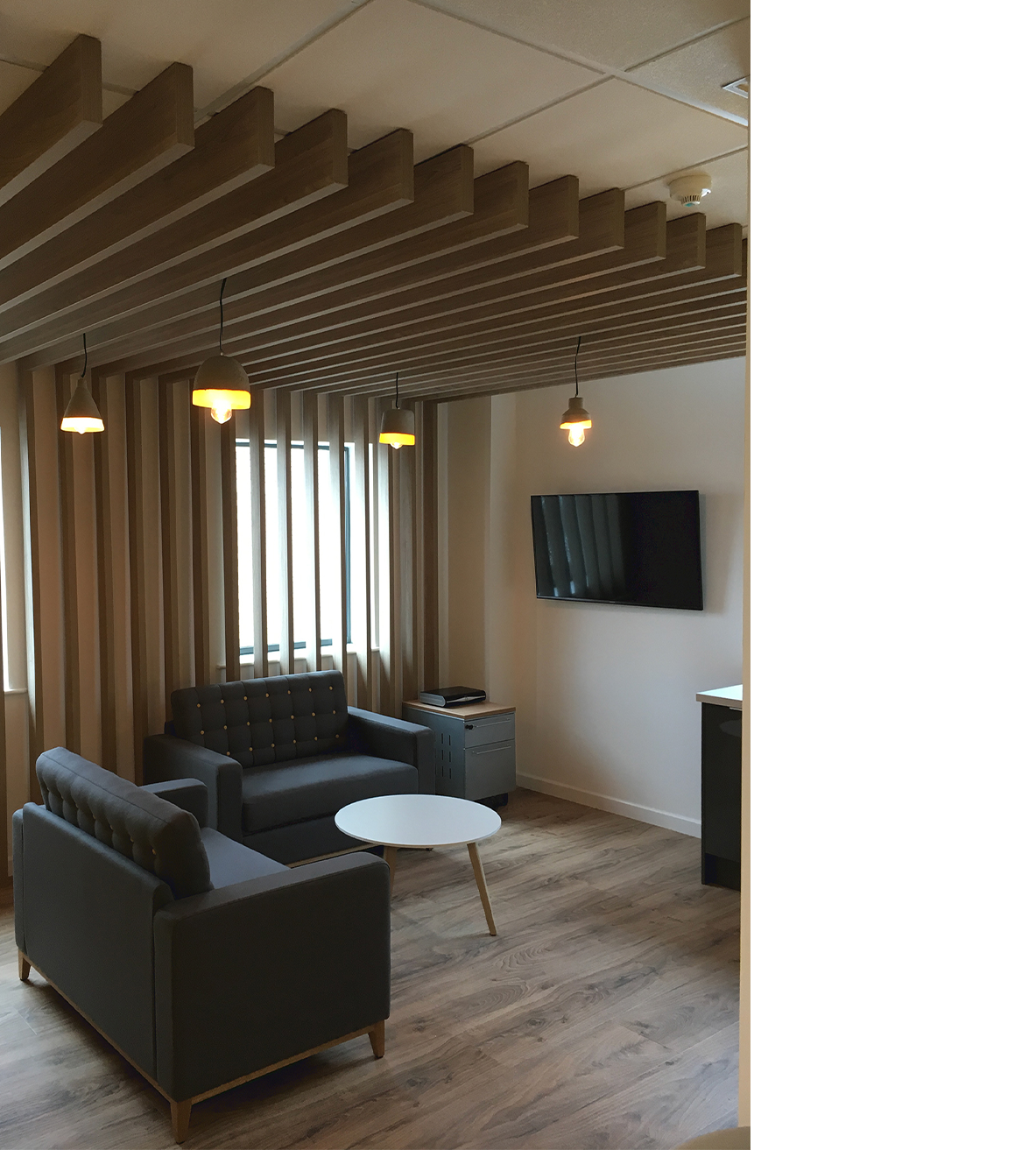 break out area with grey sofas, round coffee table and bespoke timber work