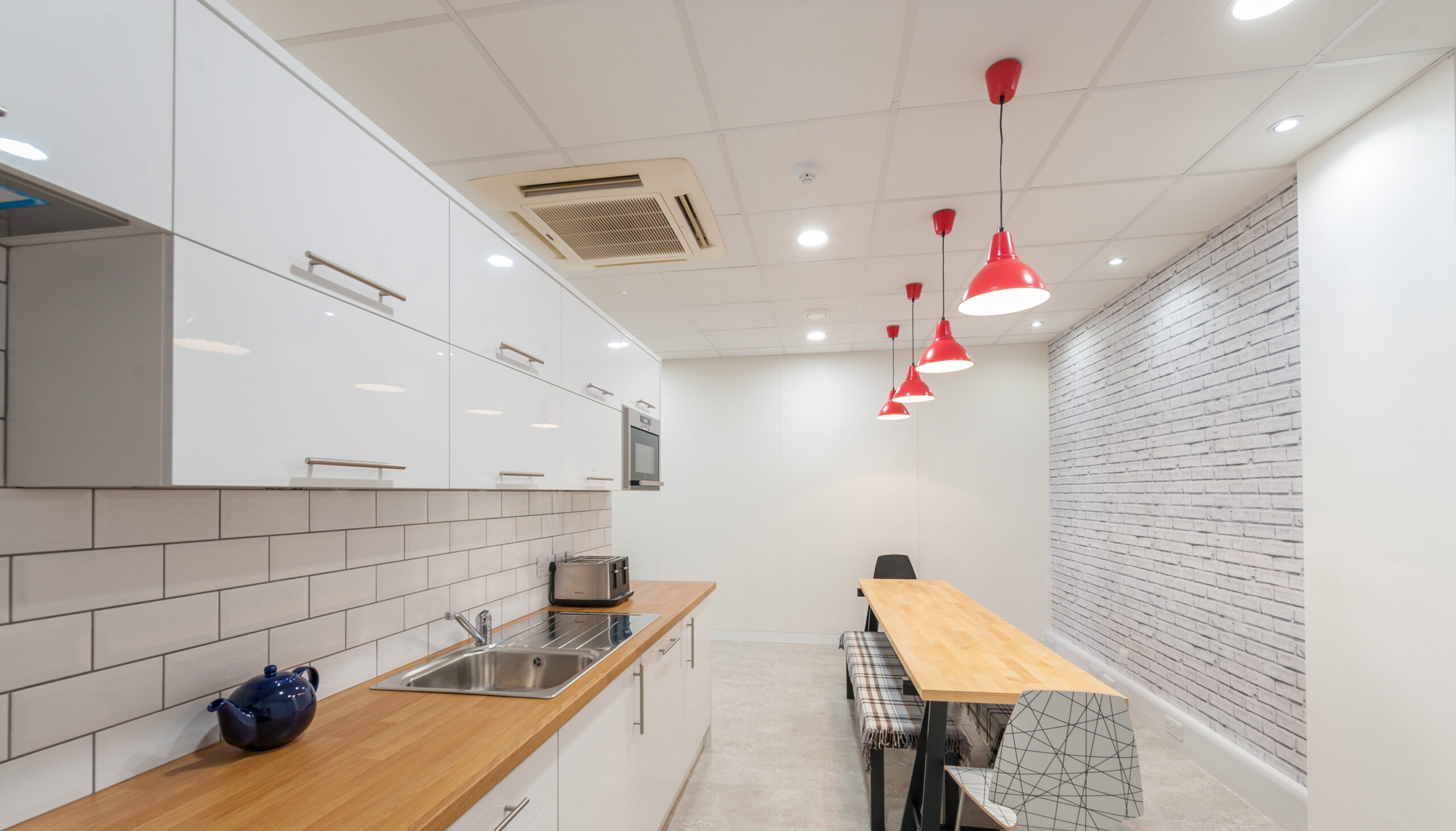 Bright white kitchen units with wooden worktop. Red pendant lighting and wooden bench style table