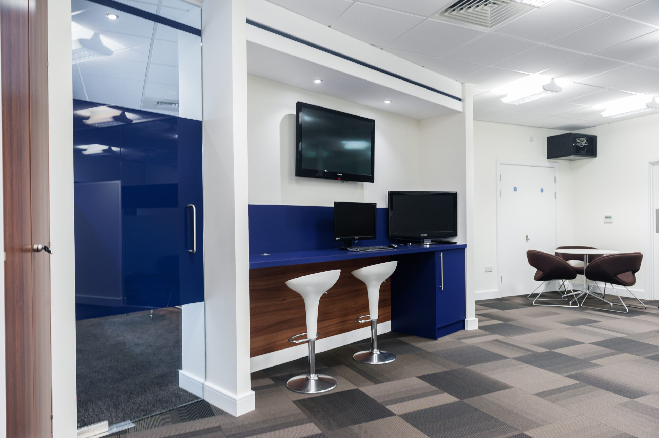 two white bar stools at blue work station with TV mounted on the wall. Carpet in square design