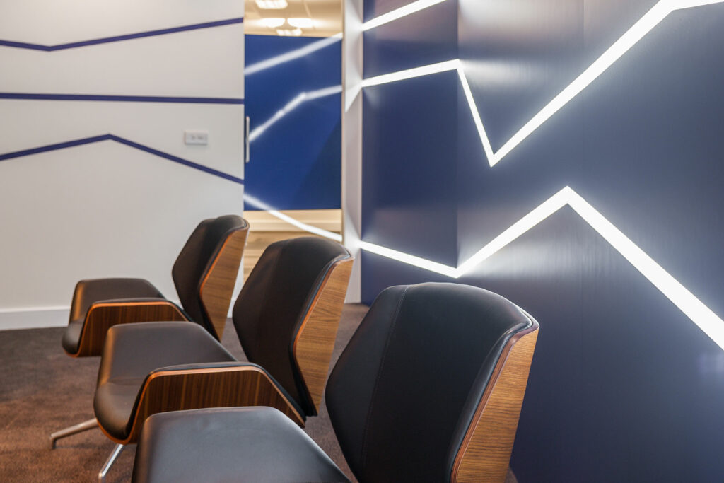 Blue wall with zig zag lighting, White wall with zig zag lighting and 3 chairs