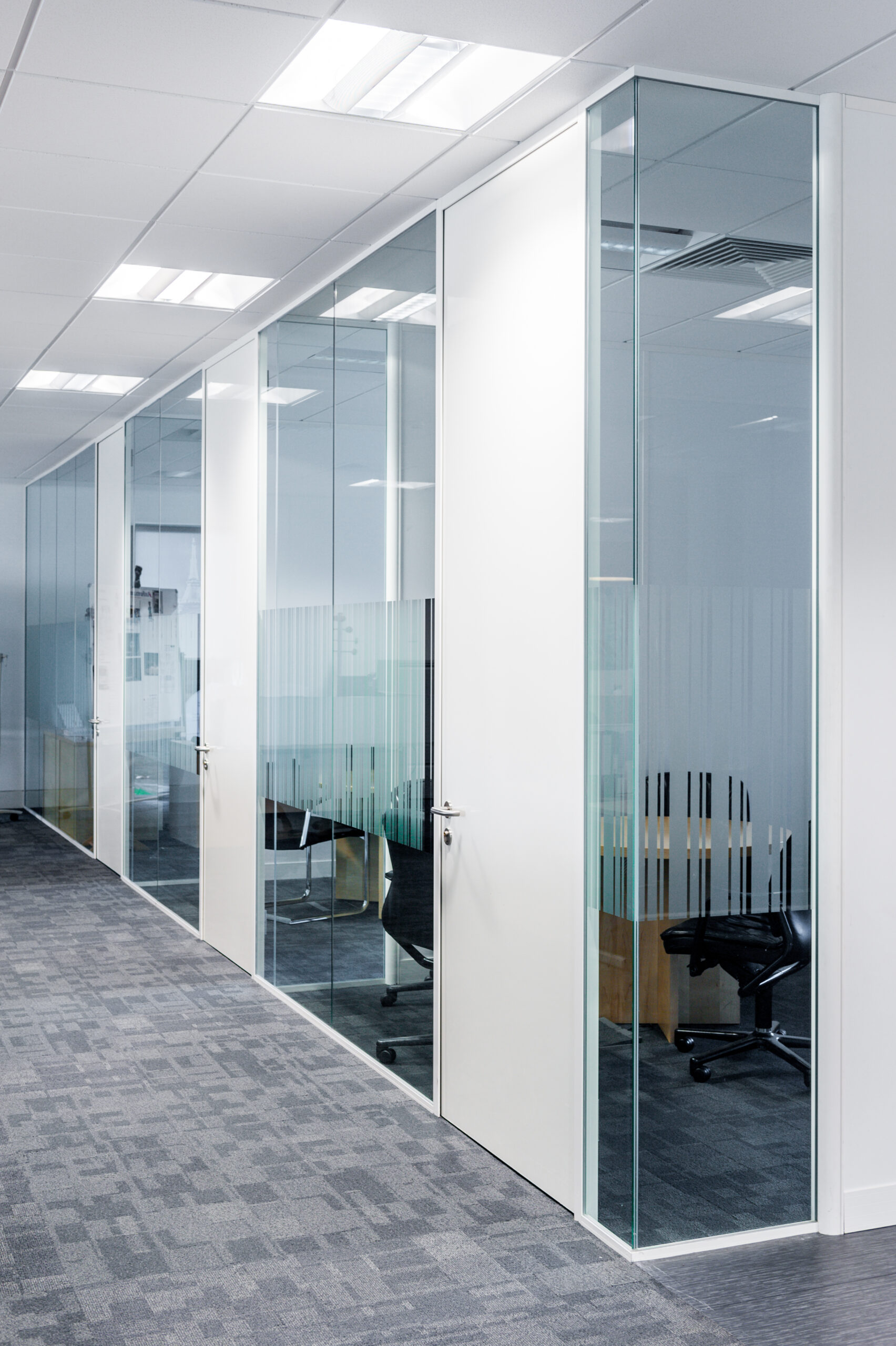 Glass partitioned offices with high white doors and manifesation on glass