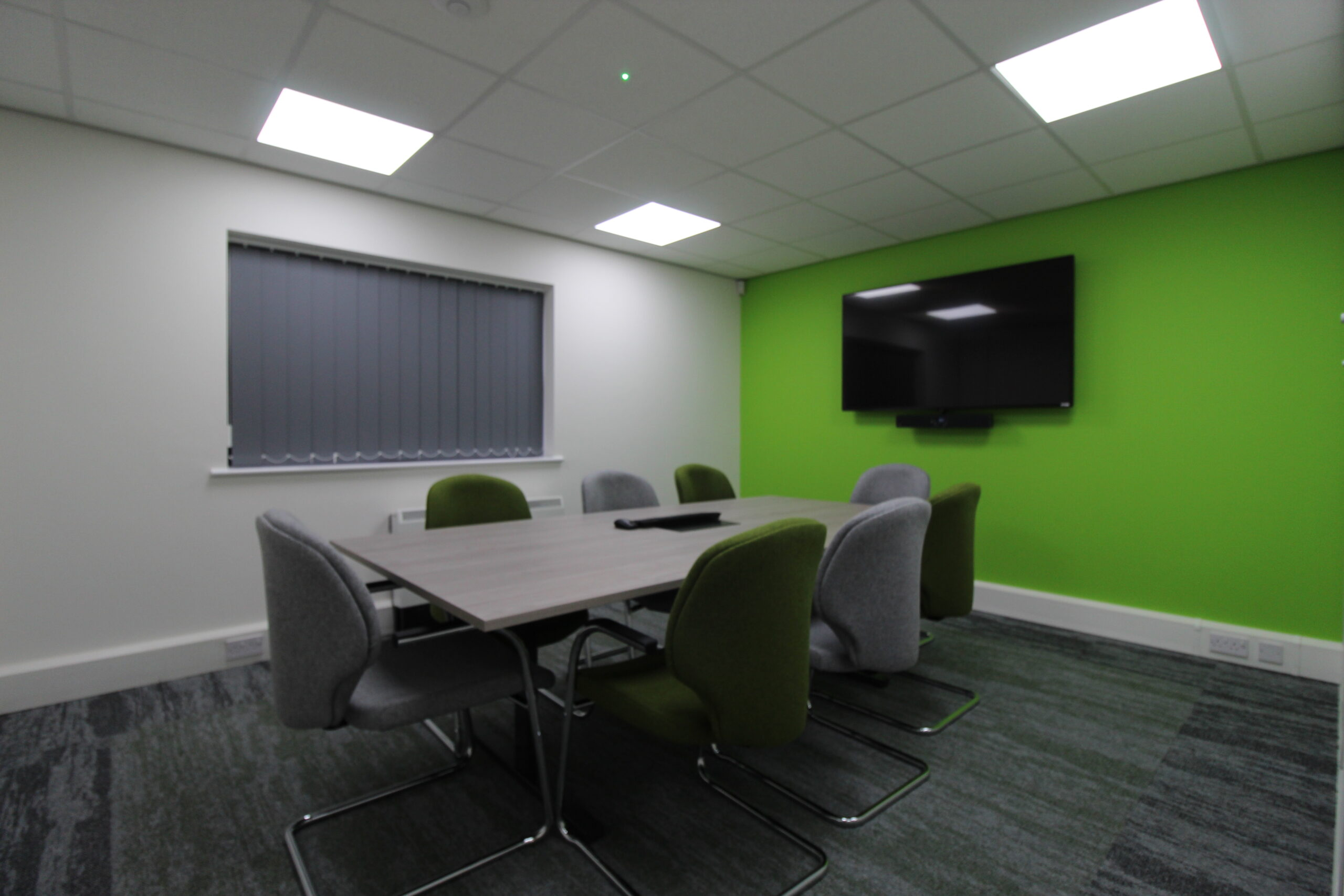 green wall with TV and boardroom table