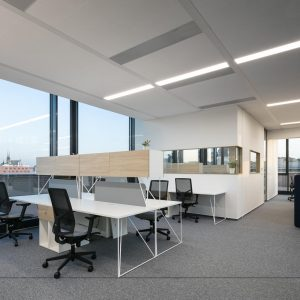bright office with white desks, mesh backed task chairs and corner office partition